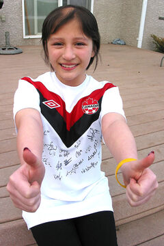 Mackenzie Ratcliffe, seen here wearing a soccer shirt autographed by members of the Canadian women's national team, has battled back from a brain tumour.