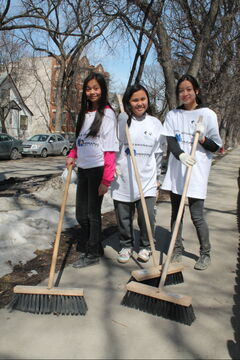 Grade 9 General Wolfe students (from left) Janela Barrera, Charlene Vivo, and Viengkham Vongkhamchanh wielding brooms on Spence Street.