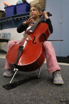 Grade 3 King Edward student Carly Gulewich learns to play Queen's We Will Rock You on cello during a Sistema practice at the school last week.