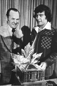 Legendary goaltender Johnny Bower (left) presents the Conn Smythe trophy for NHL playoff MVP to Philadelphia Flyers winger Reggie Leach in Montreal in June 9, 1976.