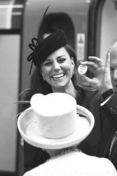 The Duchess of Cambridge shows off her 'Baby on Board' badge to the Queen.