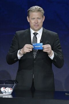 Danish former soccer goalkeeper Peter Schmeichel shows the draw of Scotland , during the UEFA EURO 2016 qualifying draw ceremony at the Acropolis Convention Centre in Nice, southeastern France, Sunday, Feb 23, 2014. (AP Photo/Lionel Cironneau)