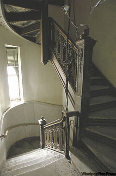 A stairwell with marble floors also boasts wrought iron and wood.