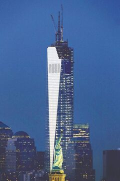 One World Trade Center rises behind the Statue of Liberty in New York.