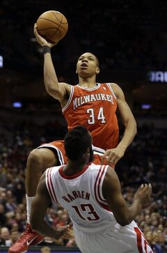 Milwaukee Bucks' Giannis Antetokounmpo (34) shoots against Houston Rockets' James Harden (13) during the second half of an NBA basketball game, Saturday, Feb. 8, 2014, in Milwaukee. (AP Photo/Jeffrey Phelps)