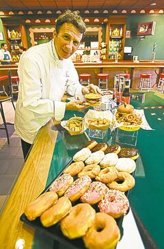 In this Sept. 5, 2013 photo, Steven Jayson, corporate executive chef at Universal Orlando displays a Chicken & Waffle Sandwich next to a Krusty Burger in The Simpsons-themed themed Moe�s Tavern at Springfield U.S.A. at Universal Orlando in Orlando, Fla. The new zone is heavy on the tasty-yet-unhealthy food featured on the show. (AP Photo/John Raoux)