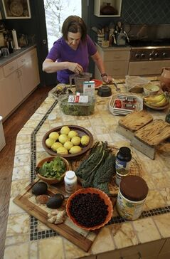 In this photo taken Friday, May 30, 2014, cookbook author Paula Wolfert makes a smoothie using avocados, cacao powder mixed with cinnamon, lemons, kale, blueberries and supplements at her home in Sonoma, Calif. Wolfert spent more than 50 years researching and writing about food. Now, she's enlisting food as an ally in a fight to stay mentally sharp. By Michelle Locke. (AP Photo/Rich Pedroncelli)