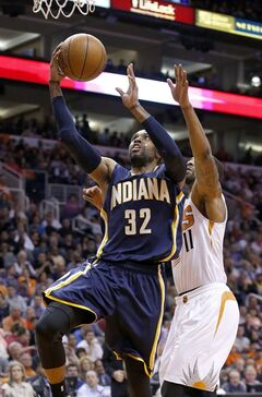 Indiana Pacers' C.J. Watson (32) scores as he gets past Phoenix Suns' Markieff Morris (11) during the first half of an NBA basketball game Wednesday, Jan. 22, 2014, in Phoenix. (AP Photo/Ross D. Franklin)