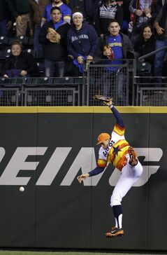 Houston Astros right fielder George Springer crashes against the wall after missing a triple from Seattle Mariners' Kyle Seager in the eighth inning of a baseball game Saturday, May 24, 2014, in Seattle. (AP Photo/Elaine Thompson)