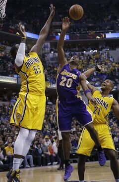 Los Angeles Lakers guard Jodie Meeks (20) looses the ball when shooting between Indiana Pacers defenders Roy Hibbert (55) and David West (21) during the first half of an NBA basketball game in Indianapolis, Tuesday, Feb. 25, 2014. (AP Photo/AJ Mast)