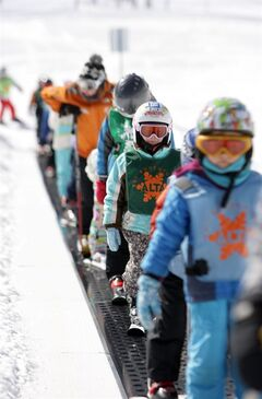 FILE - In this Feb. 19, 2013, file photo, young skiers ride the conveyor belt on Little Grizz at Alta Ski Resort in Little Cottonwood Canyon near Salt Lake City. A group of snowboarders suing to get access to Alta ski area are headed to court. The snowboarders say the ban on riding national forest land violates their constitutional rights. Alta attorneys argue snowboarding is dangerous and the suit