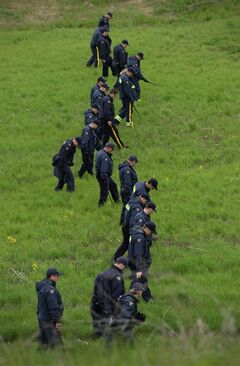 RCMP officers scour a field in Moncton, N.B. on Saturday, June 7, 2014 not far from where officers arrested a man charged with killing three of their colleagues. RCMP say a man suspected in the shooting deaths of three Mounties and the wounding of two others in Moncton was unarmed at the time of his arrest early Friday and was taken into custody without incident. THE CANADIAN PRESS/Sean Kilpatrick