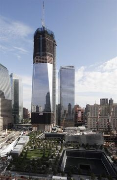 One World Trade Center overlooks the National September Memorial, Saturday, Sept. 10, 2011 in New York. Ceremonies will be held at the site Sunday for the 10th anniversary of the September 11 attacks on the United States. (AP Photo/Mark Lennihan)
