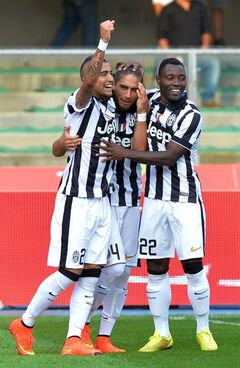 Juventus defender Martin Caceres, center, celebrates with teammates Arturo Vidal, left, and Kwadwo Asamoah after scoring his side's opening goal during a Serie A soccer match between Chievo Verona and Juventus at the Bentegodi stadium, in Verona, Italy, Saturday, Aug. 30, 2014. (AP Photo/Massimo Pinca)