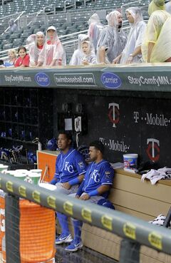 Kansas City Royals catcher Salvador Perez, left, and teammate Christian Colon, right, sit in the dugout as fans cover up during a rain delay in the fourth inning of a baseball game against the Minnesota Twins in Minneapolis, Sunday, Aug. 17, 2014. (AP Photo/Ann Heisenfelt)