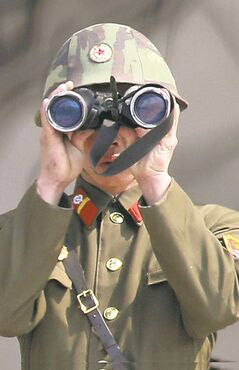A North Korean soldier uses a pair of binoculars to watch the South Korean side at the border village of Panmunjom in the demilitarized zone (DMZ) in South Korea Thursday, April 4, 2013. South Korea�s defense minister said Thursday North Korea has moved a missile with �considerable range� to its east coast, but said it is not capable of hitting the United States.