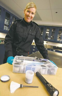 Patrol Sgt. Jennifer McKinnon with some of the tools of her job in the forensic  identification unit.