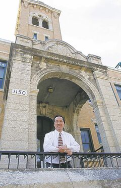 Principal Lionel Pang (above) in front of Principal Sparling School, where he was once a student.