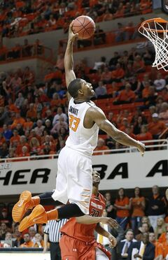 FILE - In this Feb. 22, 2014 file photo, Oklahoma State guard Marcus Smart (33) goes up for a dunk in front of Texas Tech forward Jordan Tolbert (32) in the second half of an NCAA college basketball game in Stillwater, Okla. Smart is a possible pick in the 2014 NBA Draft, Thursday, June 26, 2014 in New York.(AP Photo/Sue Ogrocki, File)