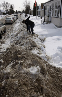 Susanne Flett tries to climb over a massive snow pile to get to her parked car on Minto Street.