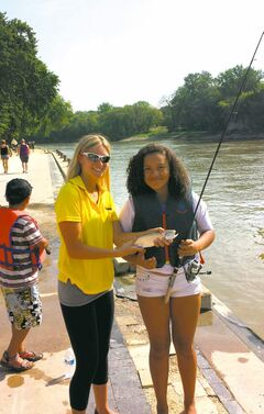Katherine Ward helps a young Fish Winnipeg angler release a goldeye caught in the Assiniboine River last Tuesday.