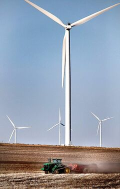 A farmer works his field near St. Leon last year. Manitoba Hydro's wind farm is seen in the background.
