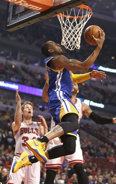 Golden State Warriors forward Andre Iguodala scores past Chicago Bulls forward Mike Dunleavy (34) and Carlos Boozer during the first half of an NBA basketball game, Wednesday, Feb. 26, 2014, in Chicago. (AP Photo/Charles Rex Arbogast)
