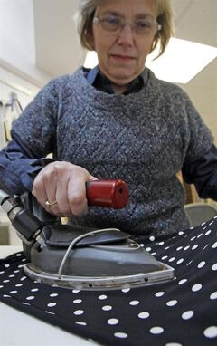 "Judy Anderson irons a dress at the Sewing Basket, Thursday, Feb. 7, 2013, in Montpelier, Vt. When toymaker Hasbro axed the clothes iron token from its Monopoly game at the suggestion of online voters – replacing it with a cat – the company implied that the small household appliance was passe: something your grandmother once used to ease the wrinkles out of socks and handkerchiefs. Even with the rise of ""wrinkle-free,"" the iron, it seems, is holding its own. While sales in the U.S. declined in volume 1 percent last year, they were up nearly 3 percent overall between 2007 and 2012, according to Euromonitor International. (AP Photo/Toby Talbot)"