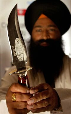 A Sikh priest displays a kirpan, a ceremonial Sikh sword, in New Delhi, India, Wednesday, Sept.1, 2004. Alberta has come up with a policy to allow Sikhs to wear a ceremonial religious dagger called a kirpan in courthouses.THE CANADIAN PRESS/AP-Manish Swarup