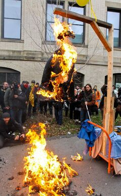 Jean Charest burns in effigy during a student demonstration against tuition increases in Montreal on Thursday.