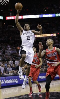 San Antonio Spurs' Kawhi Leonard (2) scores in front of Portland Trail Blazers' Damian Lillard (0) during the second half of Game 5 of a Western Conference semifinal NBA basketball playoff series, Wednesday, May 14, 2014, in San Antonio. (AP Photo/Eric Gay)