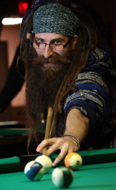 Kyle Carrier takes aim in a game of billiards at an evening meeting of the Manitoba Facial Hair Club.