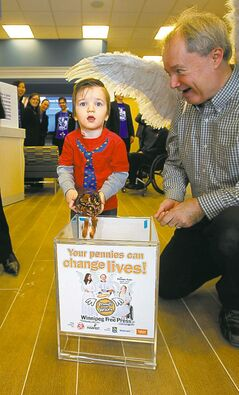 Kevin Rollason with his wings at the Sage Creek RBC event. Connel McGavock, 2.5 years old, donates his pennies. November 16, 2012  BORIS MINKEVICH / WINNIPEG FREE PRESS