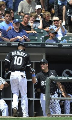 Chicago White Sox's Alexei Ramirez (10) celebrates with manager Robin Ventura (23) after scoring on a Alejandro De Aza two-RBI double during the fourth Inning of a baseball game against the Kansas City Royals in Chicago, Sunday, June 15, 2014. (AP Photo/Paul Beaty)