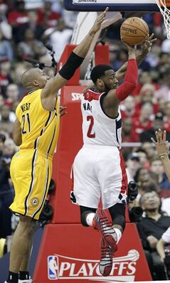 Washington Wizards guard John Wall (2) passes the ball away from Indiana Pacers forward David West (21) during the second half of Game 3 of an Eastern Conference semifinal NBA basketball playoff game in Washington, Friday, May 9, 2014. (AP Photo/Alex Brandon)