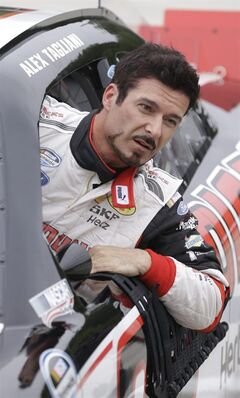 Alex Tagliani exits his race car after qualifying for the NASCAR Nationwide series auto race at Road America in Elkhart Lake, Wis, Saturday, June, 21, 2014. Tagliani won the pole position. (AP Photo/Jeffrey Phelps)