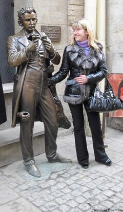 Oksana Ivanenko checks out content of pocket in statue of Leopold Von Sacher-Masoch in Lviv.