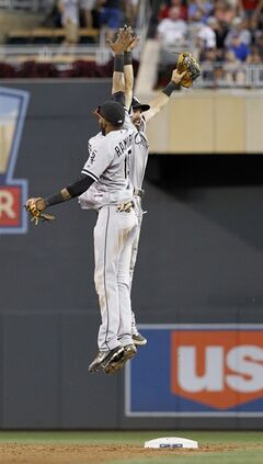 Chicago White Sox shortstop Alexei Ramirez, front, and center fielder Adam Eaton celebrate after the White Sox defeated the Minnesota Twins 7-0 in a baseball game in Minneapolis, Saturday, July 26, 2014.(AP Photo/Ann Heisenfelt)