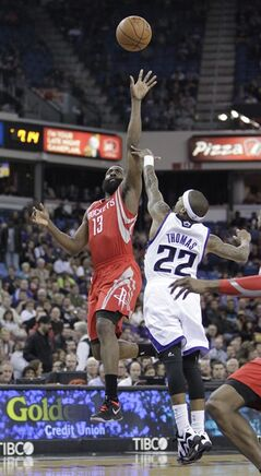 Houston Rockets guard James Harden, left, shoots over Sacramento Kings guard Isaiah Thomas during the first quarter of an NBA basketball game in Sacramento, Calif., Tuesday Feb. 25, 2014.(AP Photo/Rich Pedroncelli)