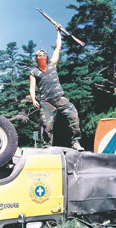 Warrior raises rifle from atop an overturned police cruiser at Oka roadblock in Quebec on July 1990.