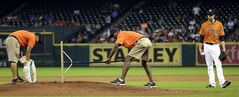 Houston Astros starting pitcher Collin McHugh (31) watches while play is stopped against the Toronto Blue Jays during the third inning of a baseball game as the grounds crew works on the pitchers mound Friday, Aug. 1, 2014, in Houston. (AP Photo/David J. Phillip)