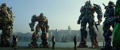 This photo released by Paramount Pictures shows, from left, Hound, Bingbing Li as Su Yueming, Stanley Tucci as Joshua Joyce, Bumblebee, Jack Reynor as Shane Dyson, Nicola Peltz as Tessa Yeager, Mark Wahlberg as Cade Yeager, Optimus Prime, Drift, and Crosshairs, in a scene from the film,