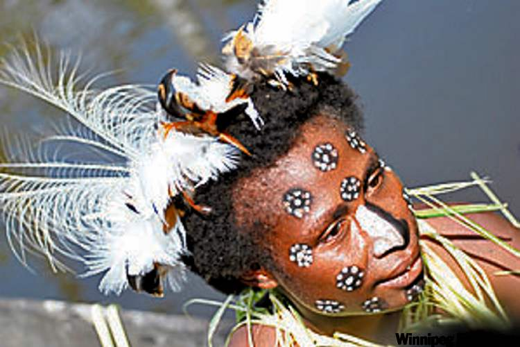 A woman in traditional dress catches piranha on the Sepik River.