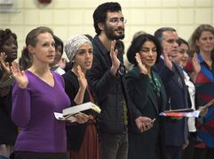 New Canadians take the oath of citizenship at a ceremony in Dartmouth on October 14, 2014. THE CANADIAN PRESS/Andrew Vaughan