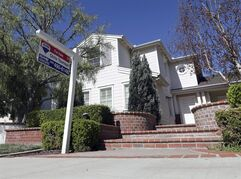In this Oct. 27, 2014 photo, a realty sign is posted in front of a home for sale in Carlsbad, Calif. Freddie Mac reports on average U.S. mortgage rates for this week on Thursday, Oct. 30, 2014. (AP Photo/Lenny Ignelzi)