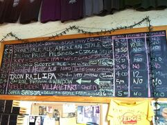 This April 19, 2015 photo shows a blackboard listing craft brews available at Wedge Brewing in the River Arts District of Asheville, N.C. The area is home to more than 180 artists who have studios and shops in old warehouses and factories. Wedge Brewing is one of a number of places to eat and drink around the vibrant neighborhood on the French Broad River. (AP Photo/Beth J. Harpaz)