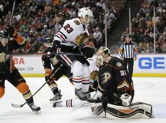 Chicago Blackhawks' Kris Versteeg, center, jumps out of the way of the puck in front of Anaheim Ducks goalie Frederik Andersen, of Denmark, during the first period of an NHL hockey game Friday, Nov. 28, 2014, in Anaheim, Calif. (AP Photo/Jae C. Hong)