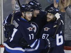Winnipeg Jets' Adam Lowry (17), Tyler Myers (57) and Michael Frolik (67) celebrate Frolik's goal against the Ottawa Senators during the third period.