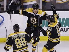 Boston Bruins left wing Milan Lucic (17) celebrates his go-ahead goal against the Florida Panthers with teammates David Pastrnak (88) and Ryan Spooner (51) during the third period of an NHL hockey game in Boston Tuesday, March 31, 2015. The Bruins won 3-2. (AP Photo/Elise Amendola)