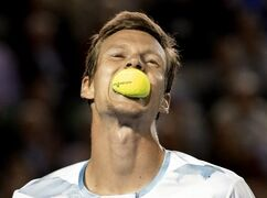 Tomas Berdych of the Czech Republic bites a ball during his semifinal match against Andy Murray of Britain at the Australian Open tennis championship in Melbourne, Australia, Thursday, Jan. 29, 2015. (AP Photo/Bernat Armangue)